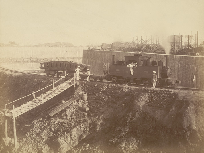 View of incline. Truck and engine with bottom girder of one gate going down to entrance [Victoria Dock construction, Bombay].